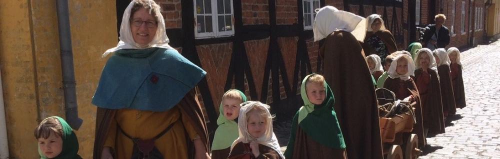 Børn i middelalderdragter på tur med formidler