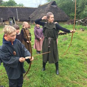 Elever i jeralderdragter skyder med bue og pil
