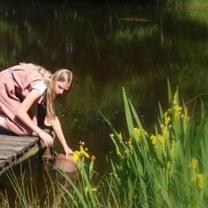 Elever i jernalderdragter henter vand i sø
