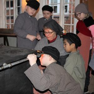 Elever ser på optænding af et gammelt brændekomfur