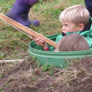 Børn leger jagt og skyder med trævåben fra en skydetønde