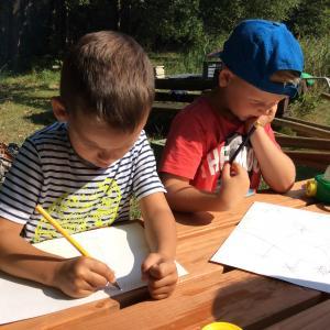 Børn tegner ved et bord